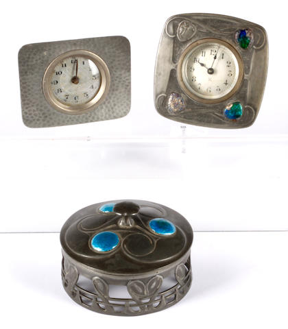 A Tudric pewter desk clock with enamelled decoration, chased with enamelled stylised leaves (some damage) stamped 0482, together with a pewter mount and cover in a similar design and a hammered desk clock. (3)