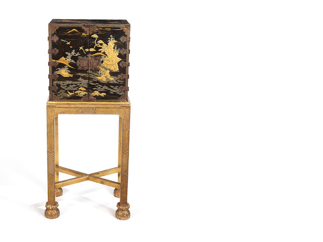 A small 18th century Japanese? black lacquered cabinet on a later carved giltwood stand