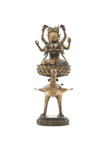 A gilt and painted bronze figure of Avalokitesvara on a peacock stand Late Ming Dynasty
