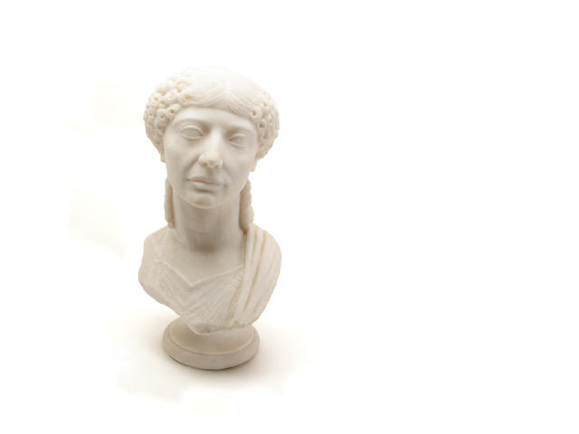 A white marble bust of a classical maiden