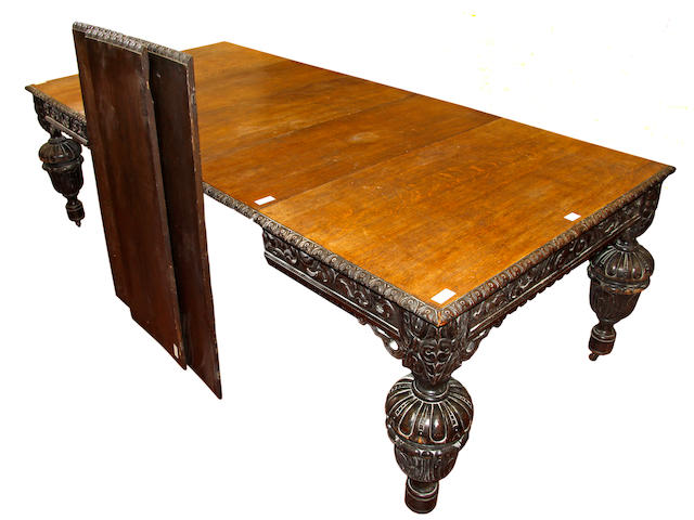 A Victorian heavy carved oak extending table and six leaves, the top with leaf carved edge and scroll frieze with pierced brackets, on substantial cup and cover legs, 356cm extended x 111cm wide.