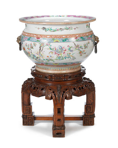 A large famille rose export porcelain fish bowl, Qianlong period, of compressed spherical form and with flaring rim, decorated with floral enameled cartouches and set with mask ring handles – Diameter: 60cms set on a circular section hardwood base with bracket feet (2)