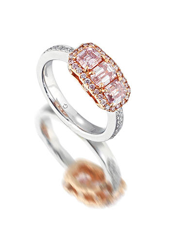 A coloured diamond and diamond three-stone ring