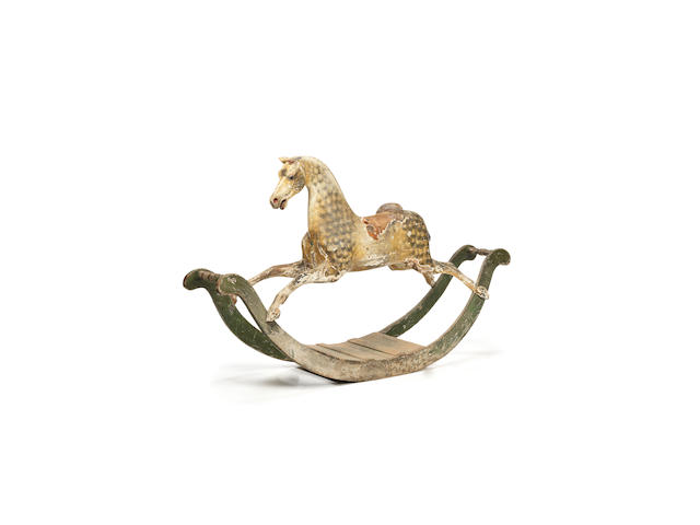A large and early 19th Century dappled grey rocking horse on bow rockers