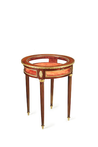 A French late 19th/early 20th century brass mounted mahogany circular bijouterie table in the Louis XVI style