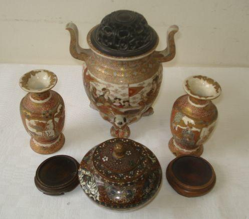 A Japanese Satsuma Koro, of ovoid shape with high side handles and resting on three figural feet and painted with ceremonial figures and Rakan, brocade border, pierced wood corner, 19cm, overall, together with a pair of small baluster vases painted with panels of figures reserved on gilt brocode ground, 10.5cm, and a Japanese cloisonne pot and cover, well decorated with lappet shaped panels of birds, butterflies and flowers on a gold stone ground, 9.5cm. (4)
