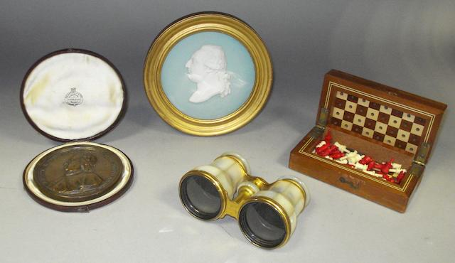 A bronze circular medallion in fitted case, a Sevres bisque portrait medallion, a travelling chess set and a pair of opera glasses.
