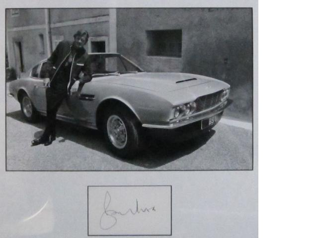 A photograph of Roger Moore with an Aston Martin DBS on the set of 'The Persuaders',