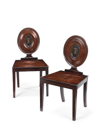A pair of late George III mahogany hall chairs