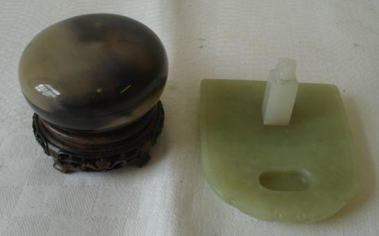 A turned polished agate pot and cover, the stone and dark grey and green grey colour, 6cm, carved wood stand and a green jade inkstand with kidney shaped well, 85cm, together with a small white jade seal surmounted by a lion dog, 33cm. (3)