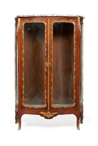 A pair of French late 19th/early 20th century gilt bronze mounted kingwood serpentine vitrines in the Louis XV style