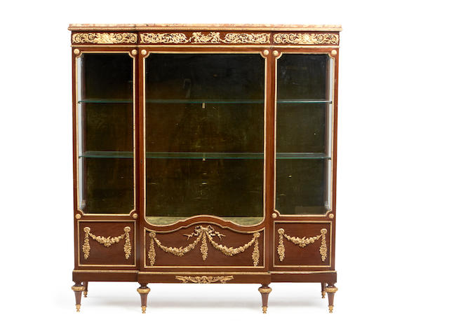 A French late 19th century ormolu mounted mahogany breakfront vitrine in the Louis XVI style
