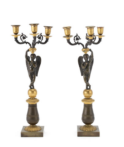 A pair of early 19th century French parcel gilt and patinated bronze three figural candelabra
