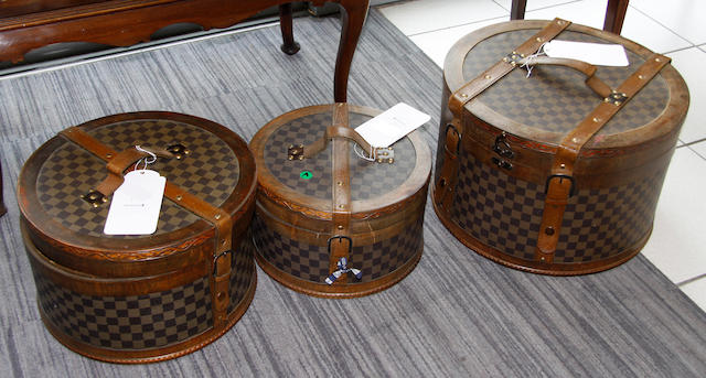 Three graduated leather and canvas covered wooden hat boxes