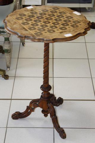A Victorian walnut tripod games table
