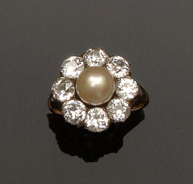A half pearl and diamond ring