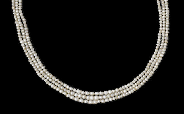 A three-strand pearl necklace with diamond-set clasp