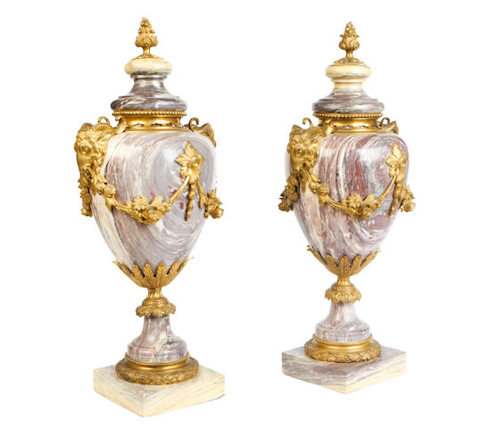 A pair of late 19th / early 20th century veined pink marble garniture urns in the Louis XVI style
