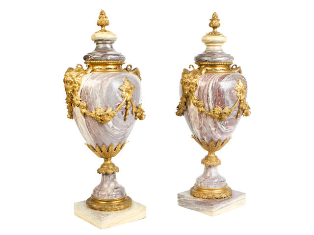 A pair of late 19th / early 20th century veined pink marble garniture urnsin the Louis XVI style