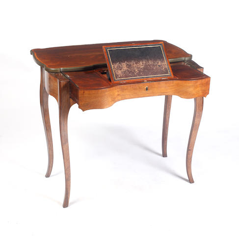 A Louis XV style rosewood and crossbanded table à ècrire, 2nd half 19th Century, the brass bound sliding top of shaped outline, the pull out frieze fitted with an adjustable inset writing slope enclosing two small drawers flanked by a pair of compartments with hinged covers, on cabriole legs, 86 x 44cm.