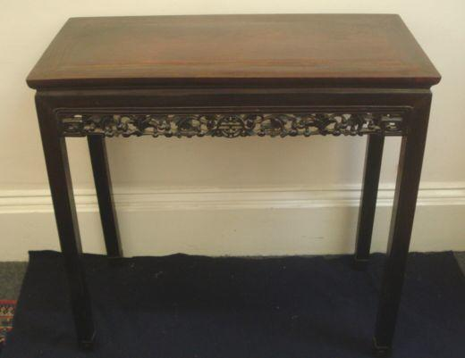 A Chinese rosewood side table, the rectangular top above friezes carved and pierced with fruiting branches centred by a 'shou' medallions, on moulded square section legs, 91 x 45cm.
