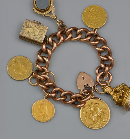 A 9ct gold curb-link bracelet suspending assorted coins and fob seals