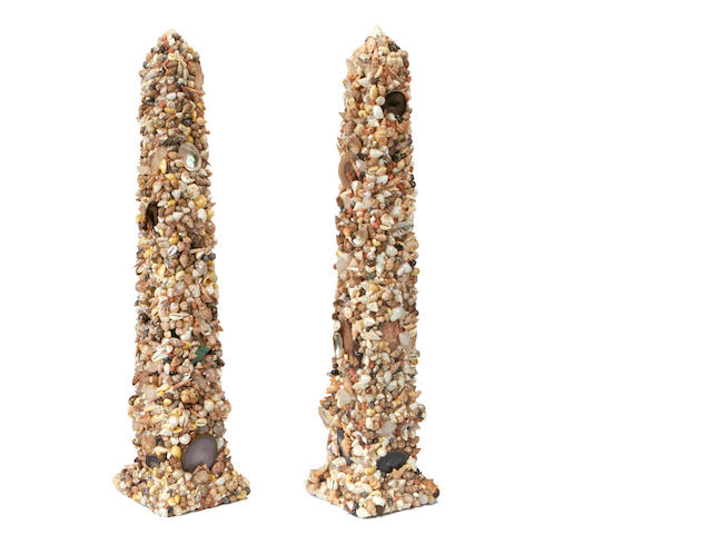 A pair of shell encrusted obelisks