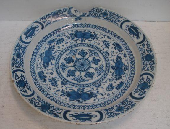 A Delft blue and white charger, painted with leaves and fruits around a central flowerhead roundel, the border with remains of initials and date 1700, 38.5cm.
