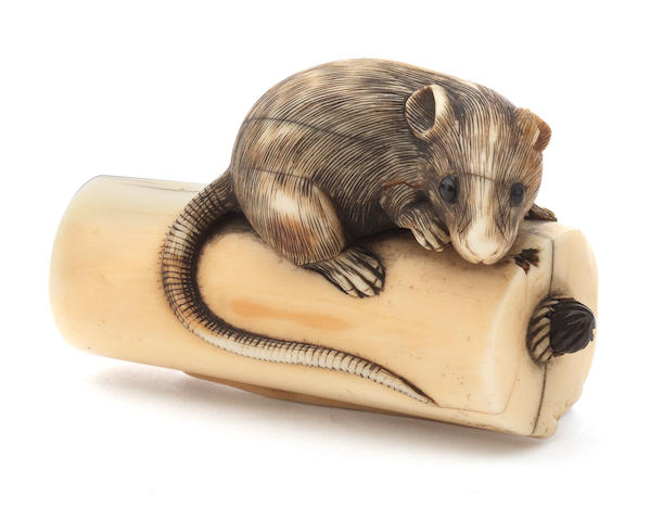 An ivory netsuke of a rat on a candle Kyoto, early 19th century