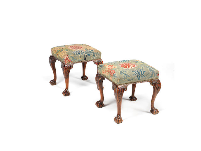 A pair of George II carved walnut stools