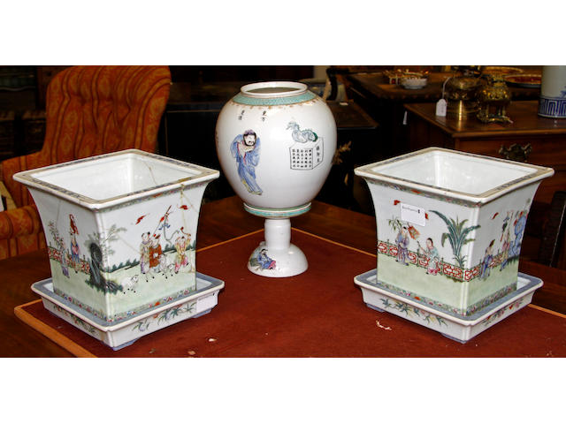 A Pair of Chinese 'famille rose' Jardinieres and Stands,red four character seal marks, square tapering, painted around the sides with igures and animals in a fenced garden, 20cm, and a 'amille rose' table lamp and shade painted with figures and calligraphic inscriptions, 30cm. (6).