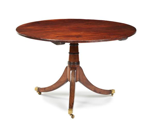 An early 19th century mahogany oval tilt top table
