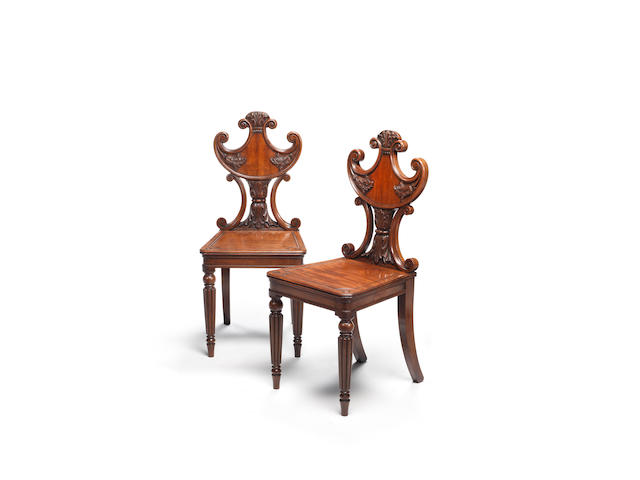 A pair of Regency carved mahogany hall chairs in the manner of Gillows