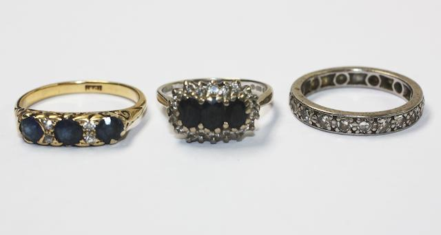 A diamond full hoop eternity ring and two sapphire and diamond rings, (3)