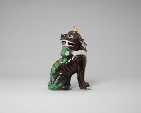 A Chinese famille verte biscuit model of a seated horned mythical beast, 19th/20th century