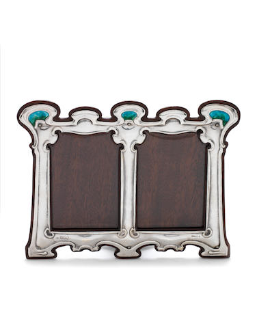 An Edwardian Art Nouveau silver and enamelled double photograph frame by Messrs Hutton & sons, London 1903