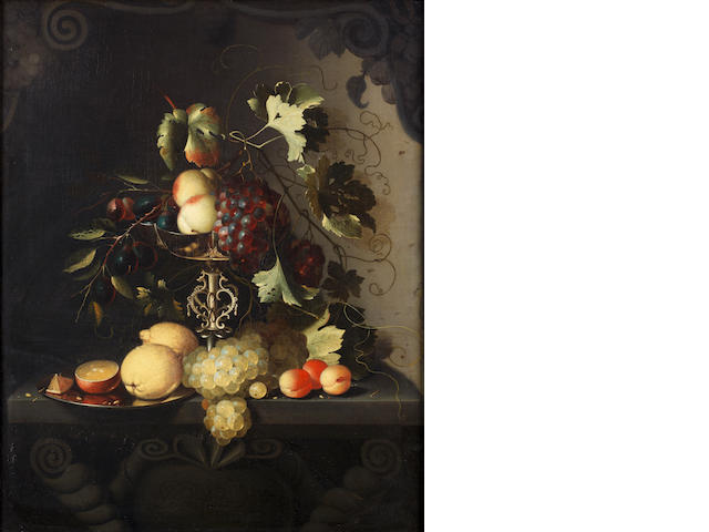 Laurens Craens (The Hague circa 1620-circa 1670 Middleburg) Peaches and grapes draped over a silver tazza with lemons, oranges and apricots on a stone ledge