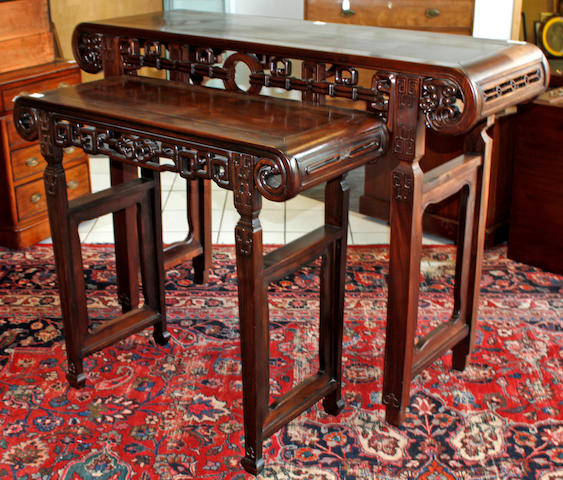 A Chinese carved hardwood alter table,with scrolled ends and pierced frieze on square section legs, 144cm wide and a very similar smaller table, 100cm wide (2)