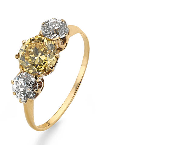 A fancy vivid yellow diamond and diamond three-stone ring
