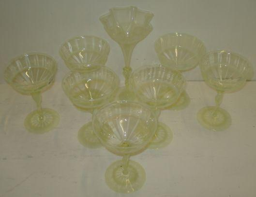 A set of seven James Powell & Sons champagne glasses, probably designed by Harry Powell in 'straw opal' glass, 14cm, together with a Venetian inspired vase with thrown rim, 20cm, pattern 837.See Lesley Jackson Whitefriars glass plate 19 page 101 for similar examples.