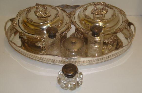 A late Victorian silver mounted cut glass inkwell, John Grinsell & Sons, Birmingham 1893, with hinged cap and compressed circular star cut base, an engine turned silver mounted cut glass powder bowl with interior mirror, a pair of continental silver mounted oval cut glass toilet jars, English Import marks for 1910, with screw caps, also a pair of Old Sheffield plate circular entree dishes with two handled warming bases, acanthus borders, scroll feet and detachable handles, 30cm across and an oval George III style gallery tray. (7)