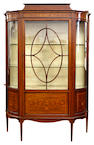 An Edwardian mahogany boxwood and ebony strung display cabinet, satinwood crossbanded and inlaid with ribbon tied drapes, musical emblems, classical urns and leaf scrolls, the glazed central door flanked by glazed elliptical sides, panelled below, on square tapered legs, 123cm.