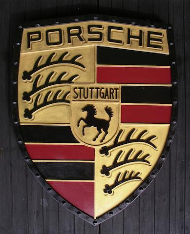 A hand-painted Porsche garage display emblem,