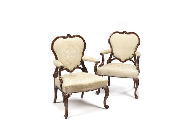A pair of George III mahogany Gainsborough armchairs in the manner of Thomas Chippendale