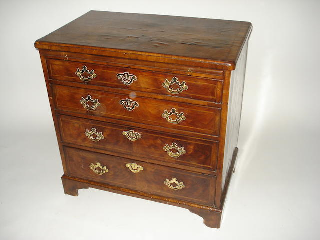 A George I walnut featherbanded and crossbanded chest of drawers