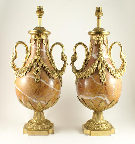 A pair of 19th century style veined pink marble and gilt-bronze mounted urns in the form of lamp stands.