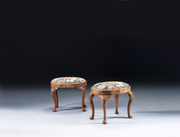 A pair of George I carved walnut stools oval stools upholstered in 18th century needlework
