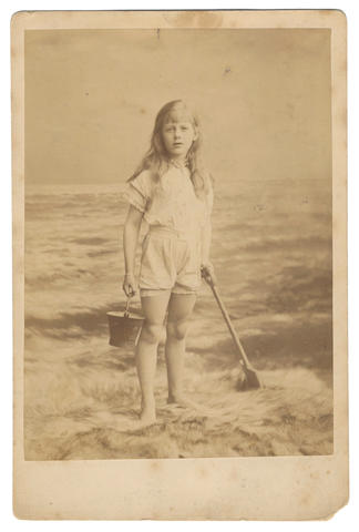 DODGSON (CHARLES LUTWIDGE) Photograph of a young girl with bucket and spade at the seaside, bearing his autograph endorsement in violet ink, Eastbourne, 1883