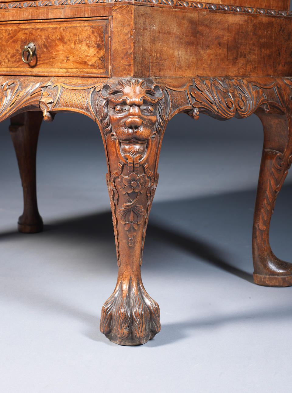 A George II carved walnut and burr walnut crossbanded and featherbanded bureau on stand