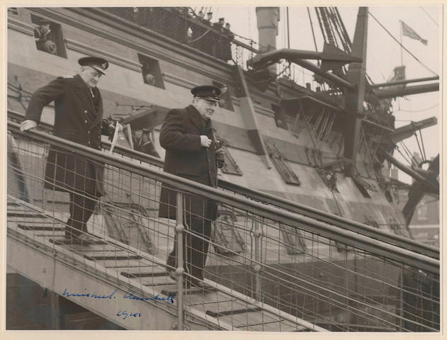 """CHURCHILL (WINSTON) Photograph signed and dated (""""Winston S. Churchill/ 1941""""), taken by the official War Office photographer, showing Churchill, in Trinity House uniform, descending the gangplank of HMS Victory followed by Admiral Sir William Milbourne James, [HMS Victory, Portsmouth Docks, 31 January 1941]"""